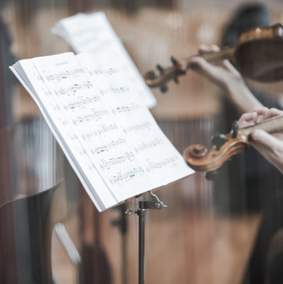 Détails de violons à travers les cordes d'une harpe